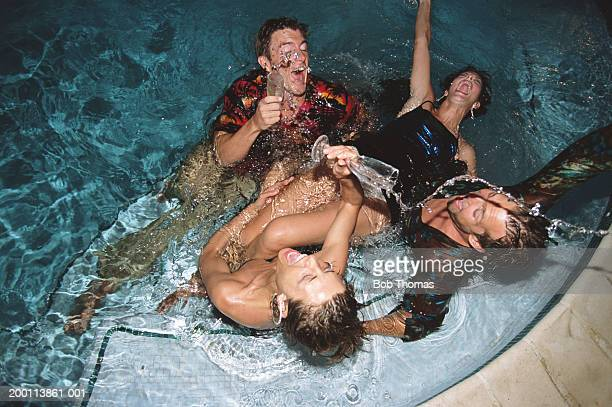 Four fully clothed young people splashing in pool, elevated view