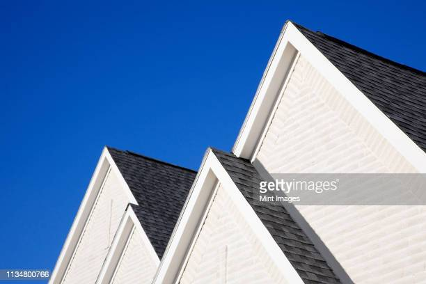 four gabled rooflines - rooftop stock pictures, royalty-free photos & images