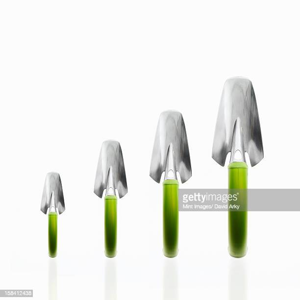 Four garden trowels with green handles and metal tops, in ascending size order.