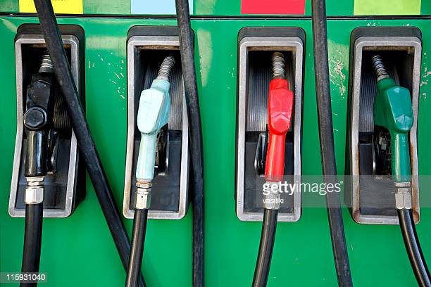 Four gas pumps with black, white, red and green nozzles