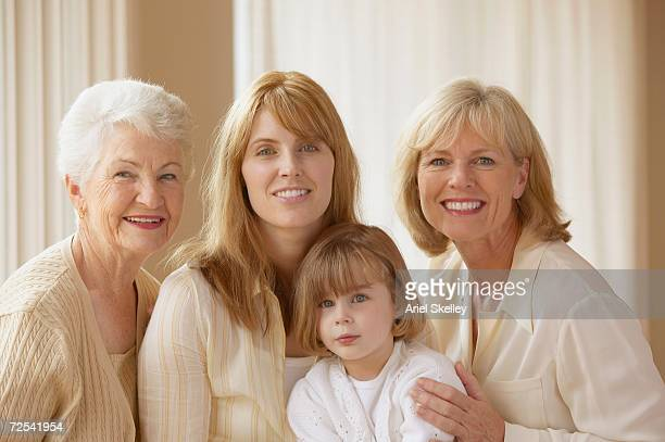 Four generations of female family members smiling