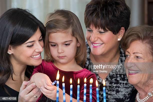 Four generations of women lighting Hanukah menorah
