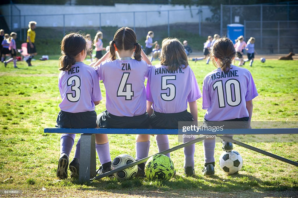 four girls [8] on the bench at soccer game : Stock Photo