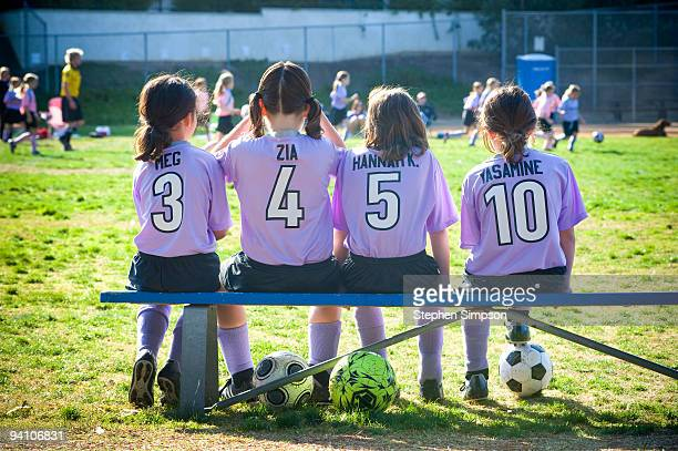 four girls [8] on the bench at soccer game