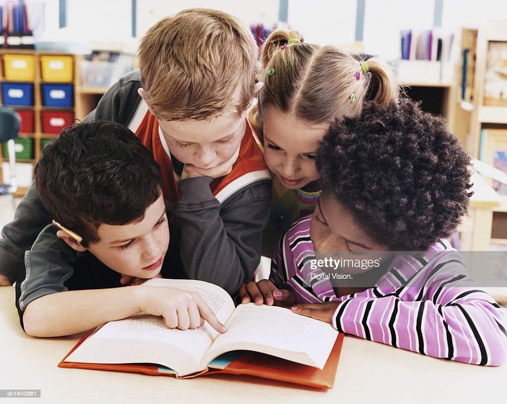 Four Girls and Boys Looking at the Same Textbook in a Classroom at Primary School : Stock Photo