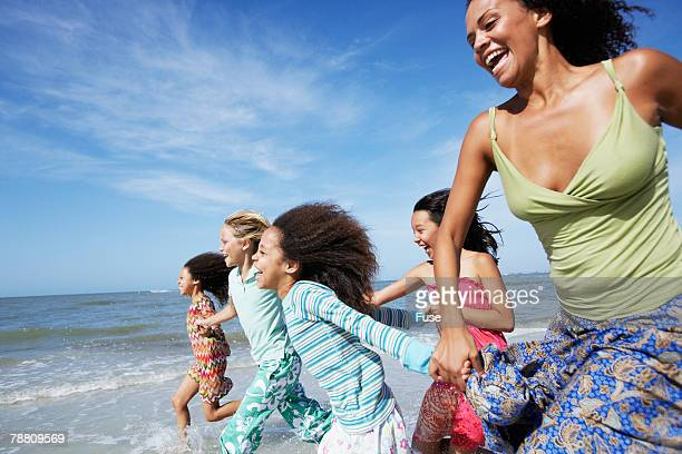 four girls and woman running on beach - 日常から抜け出す ストックフォトと画像