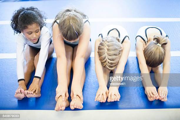 Four girls doing gymnastics exercise on floor