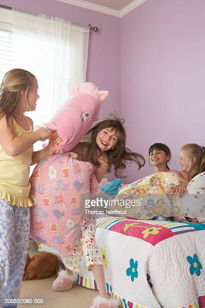 Four girls (8-10) having pillow fight at slumber party