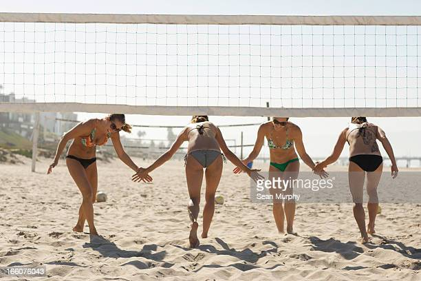 four girls high fiving under volleyball net - older woman bending over stock pictures, royalty-free photos & images
