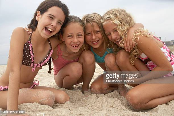four girls (8-12) huddling together on beach, laughing, portrait - one piece swimsuit stock pictures, royalty-free photos & images