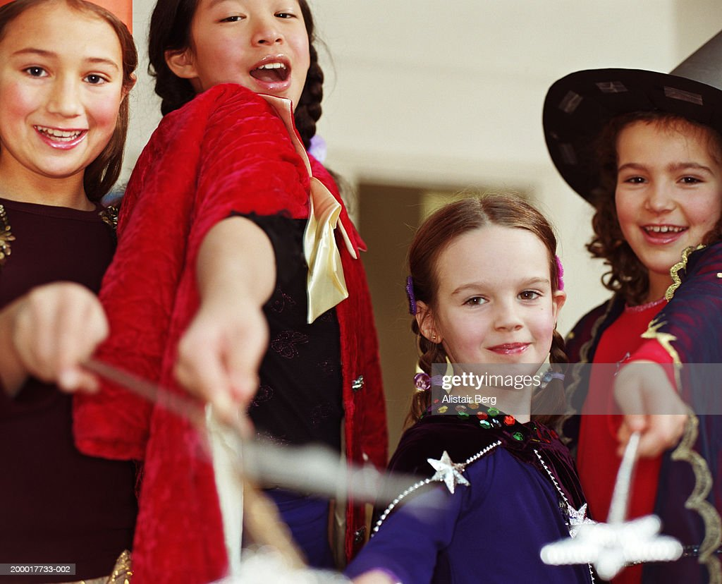 Four girls (6-8) in witch costumes waving wands, portrait, close-up : Stock Photo