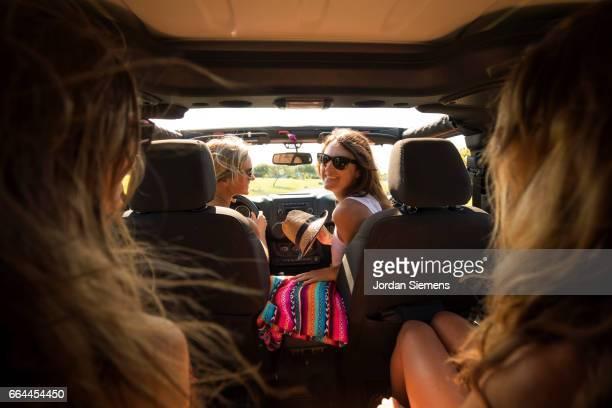 four girls riding in a jeep. - viaggio in macchina foto e immagini stock