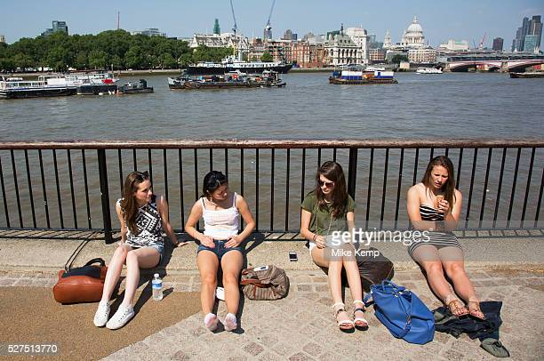 Four girls sitting in the sun beside the River Thames on the Southbank, London, UK. This is a popular place for Londoners to come and hang out...