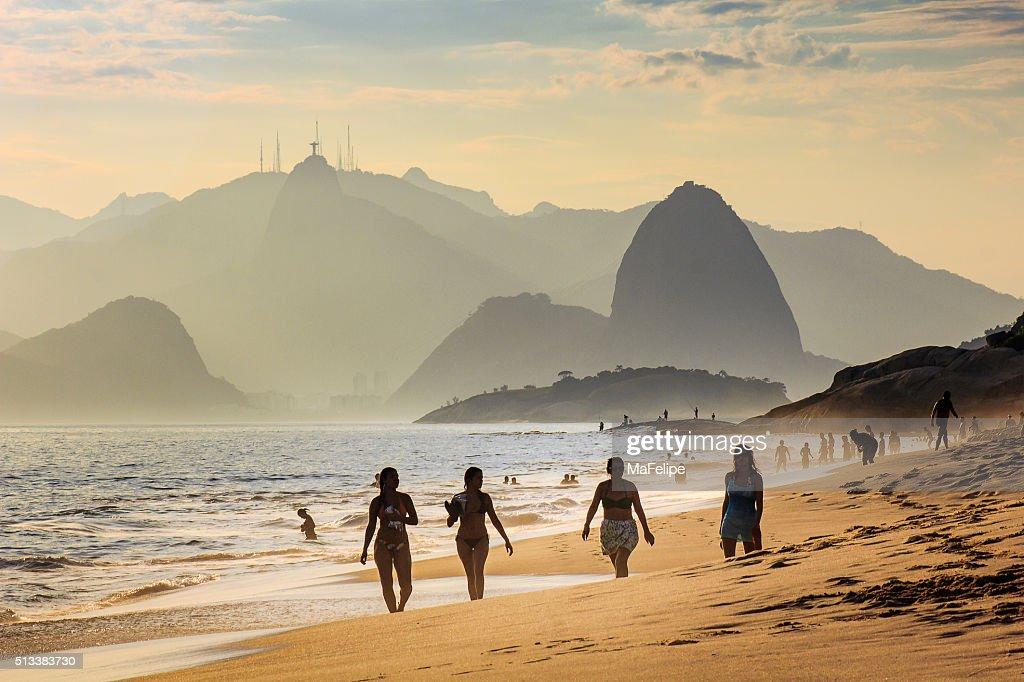 Vier Mädchen Spaziergang am Strand bei Sonnenuntergang : Stock-Foto