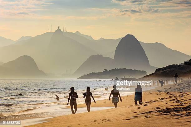 Vier Mädchen Spaziergang am Strand bei Sonnenuntergang