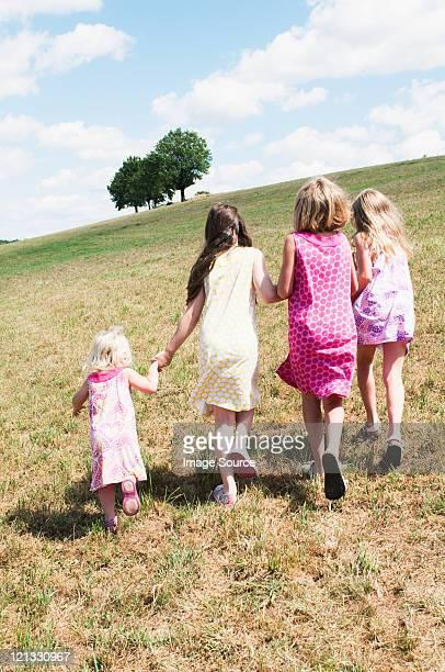 Vier Mädchen zu Fuß in Feld