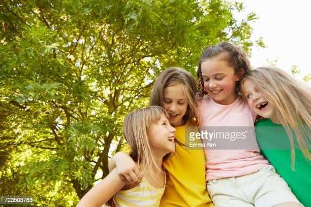 Four girls with arms around each other in park