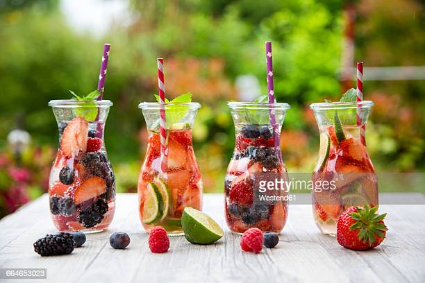 Four glass bottles of detox water infused with different fruits