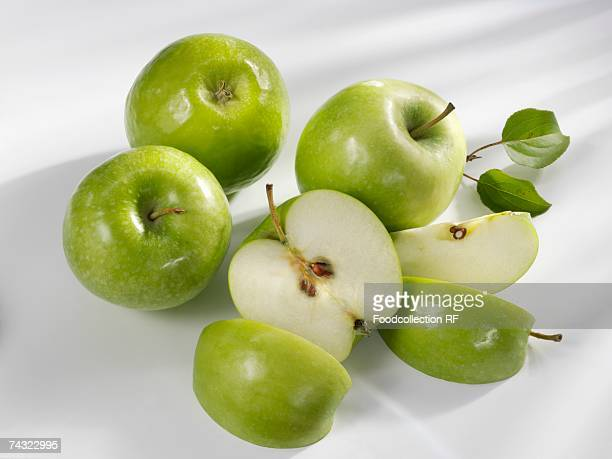 Four 'Granny Smith' apples, one cut into pieces