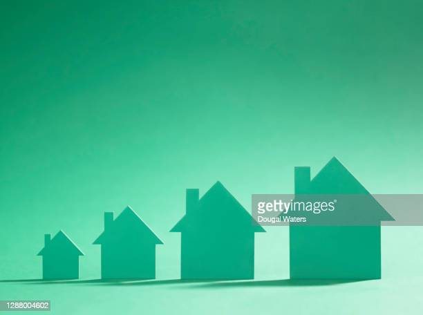 four green cardboard cutout houses on green background of increasing size. - consumerism stock pictures, royalty-free photos & images
