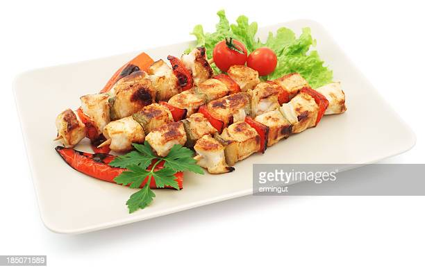 Four grilled chicken kabobs with salad on plate - isolated