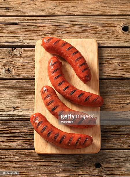 four grilled sausages on wooden table - sausage stock pictures, royalty-free photos & images
