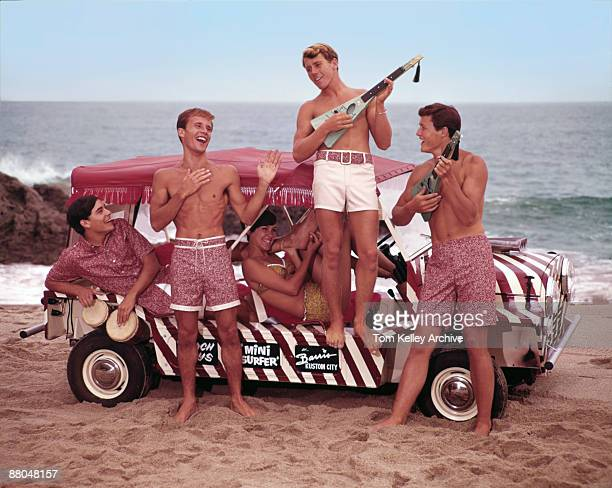 Four guys and a girl all students sit or stand next to a Barris surf car while wearing the latest fashion in Jantzen bathing suits California 1966