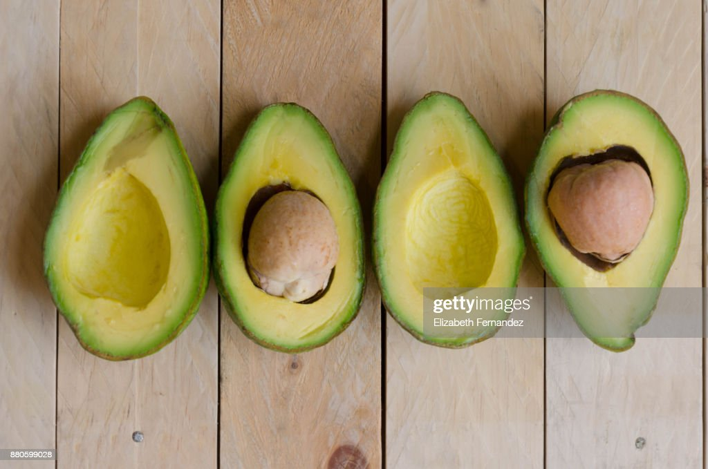 Four halves of avocados on wood background : Stock Photo
