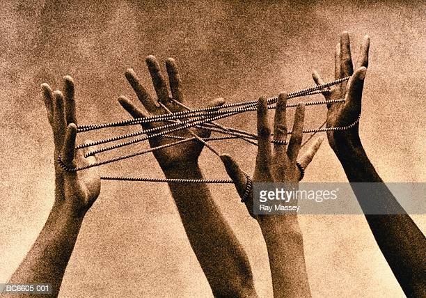 Four hands connected by cord, forming 'cat's cradle' (toned B&W)