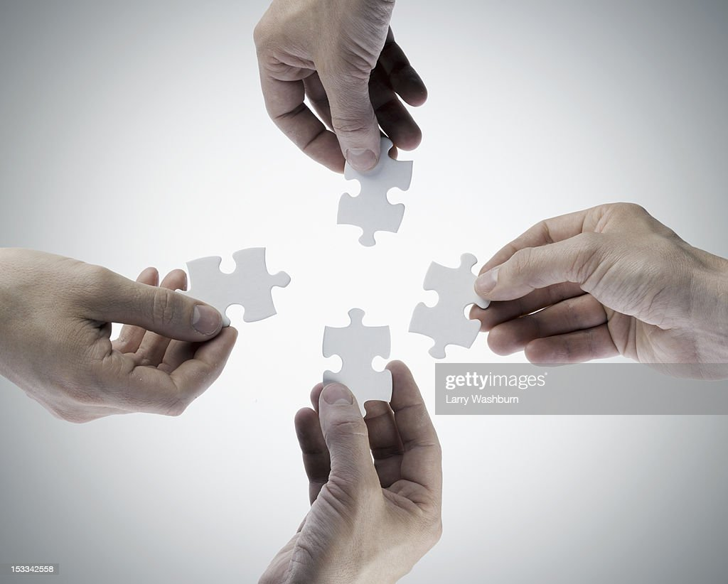 Four hands holding jigsaw puzzle pieces, directly above : Stock Photo