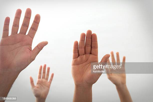 Four hands rises up on off white background