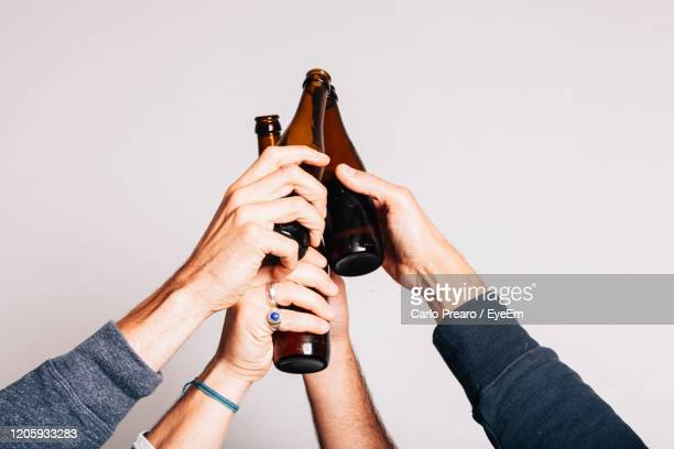 four hands toasting together. friendship, carefree, togetherness concept. - celebratory toast stock pictures, royalty-free photos & images