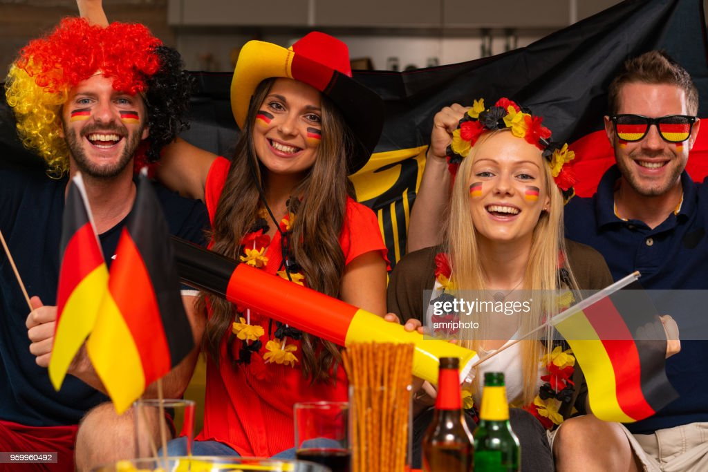 four happy german soccer fans at home : Stock Photo