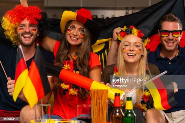 vier glückliche deutsche Fußball-Fans zu Hause