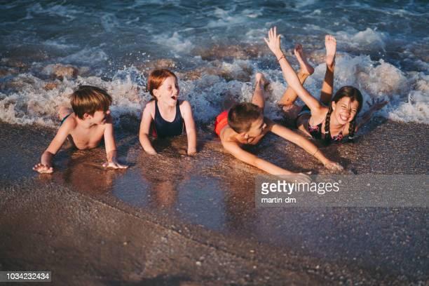 fyra glada barn liggande på stranden - värmebölja bildbanksfoton och bilder