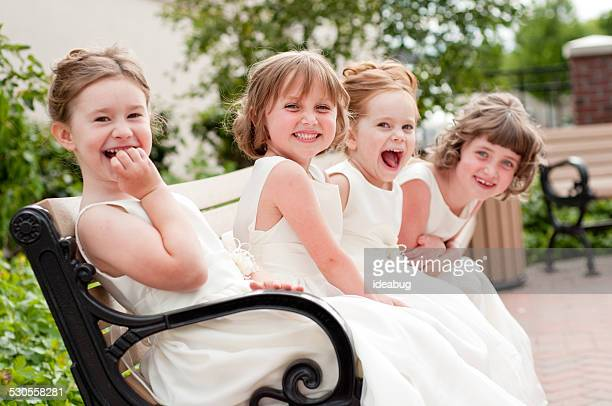 four happy little flower girls laughing together in formal dresses - wedding ceremony stock photos and pictures