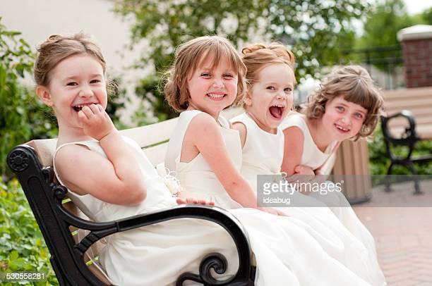 Happy Little flor cuatro chicas Riendo juntos en vestidos Formal