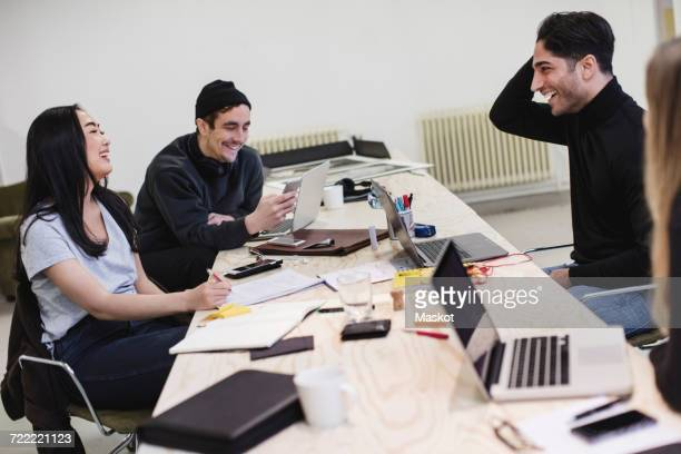 Four happy people sitting at desk in office