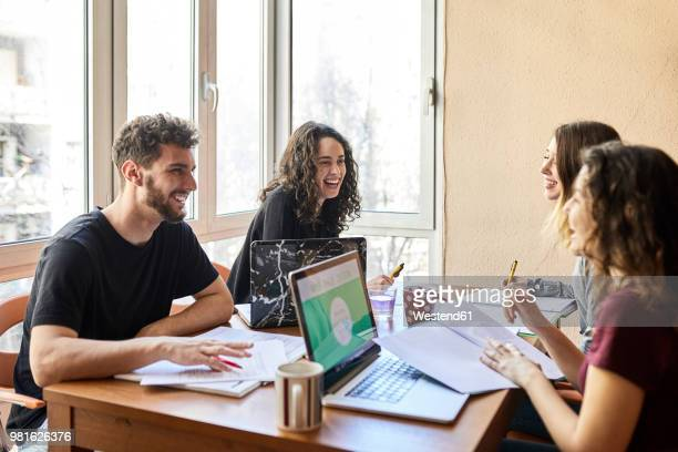 four happy students at desk learning together - lernen stock-fotos und bilder