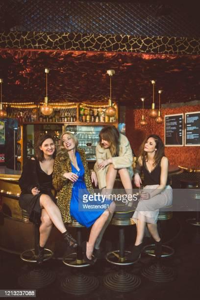 four happy women sitting at the bar in a club - イブニングウェア ストックフォトと画像