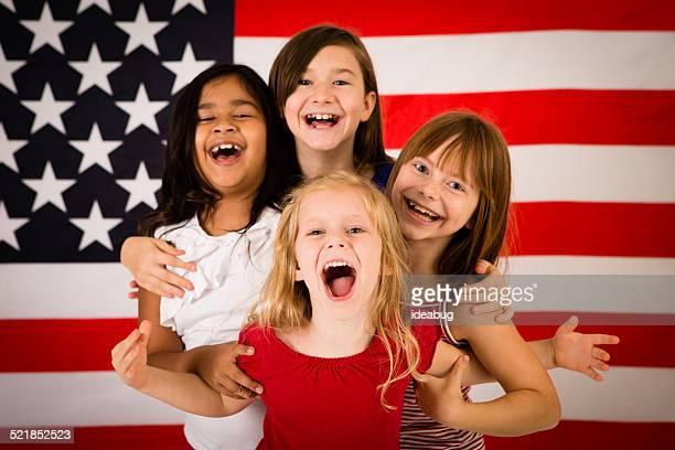 4 つの幸せな若い女性の前に、アメリカの旗