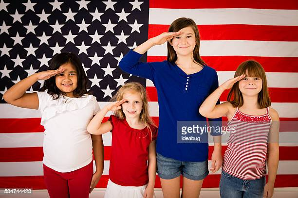 Four Happy Young Girls Saluting in Front of American Flag
