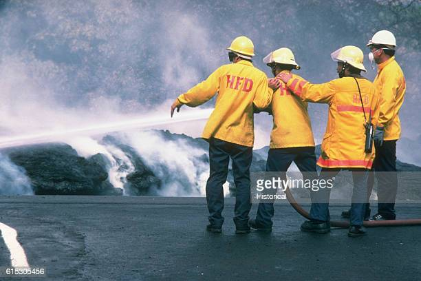 Four Hawaiian firefighters attempt to put out a burning lava flow shortly after a volcano erupts