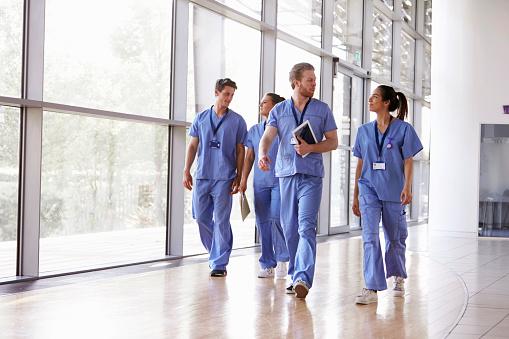 Four healthcare workers in scrubs walking in corridor 862725544