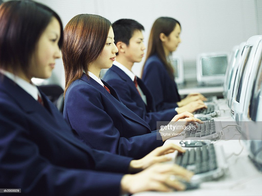Four High School Students Sitting in a Classroom Using Computers : Stock Photo