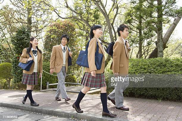 Four high school students walking down the street, smiling