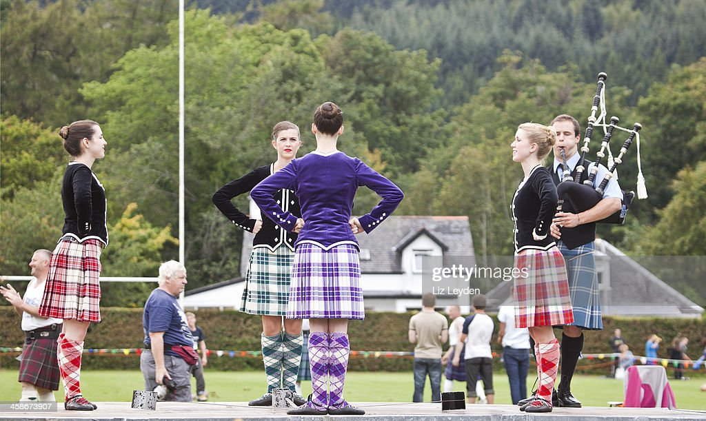 Four highland dancers doing Sword Dance with Piper : Stock Photo