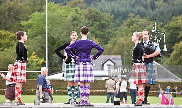 Four highland dancers doing Sword Dance with Piper
