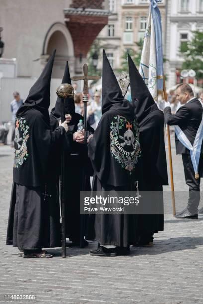four hooded men during corpus christi feast in krakow, poland - only men stockfoto's en -beelden