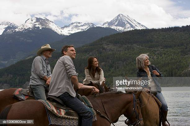 Four horse riders by river looking at view, mountains in background